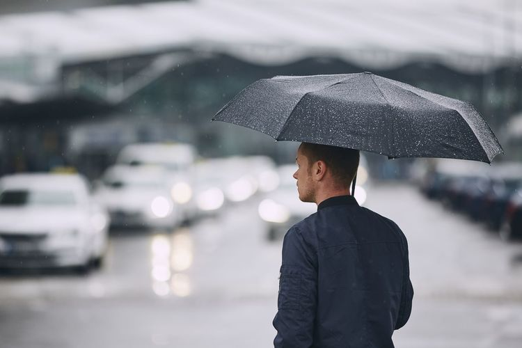 Rear view of man with umbrella standing on road during rainfall