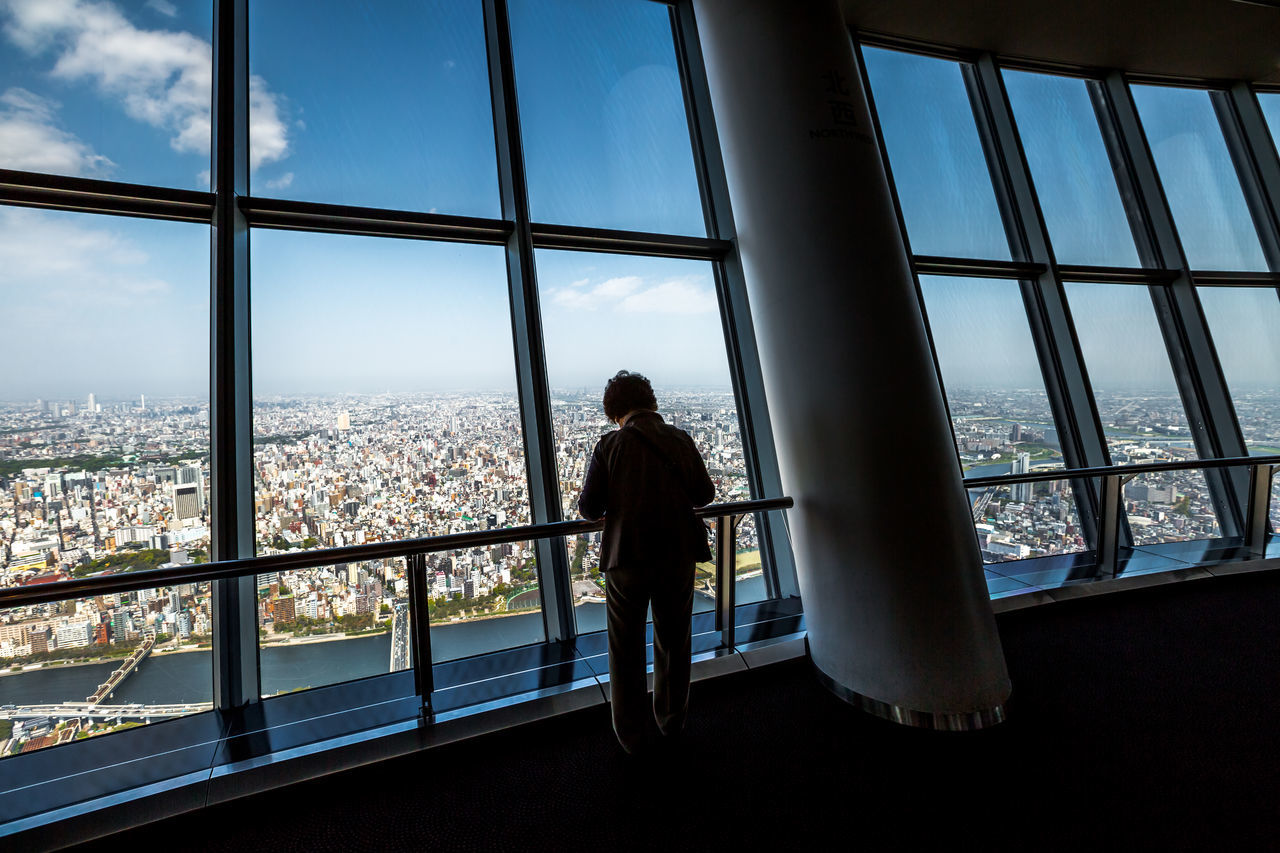 window, transparent, architecture, glass - material, built structure, real people, one person, city, standing, indoors, cityscape, looking through window, building, rear view, day, nature, men, looking, looking at view, window frame, skyscraper