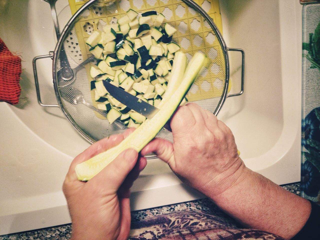 Cropped Image Of Person Slicing Cucumber In Container