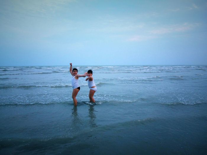 Siblings Dancing At Beach Against Sky