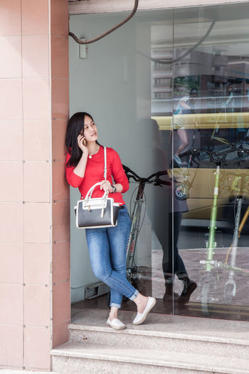 young woman in the city with the phone City Bag Beautiful Woman Call Casual Clothing Citylife Day Full Length Holding One Person People Phone Real People Smiling Standing Talk Young Adult Young Women