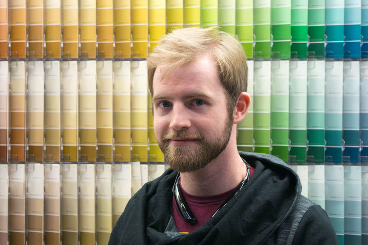Portrait of smiling mid adult man against color swatch at store