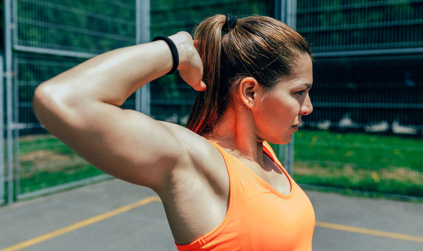 Thoughtful female athlete exercising on court against fence