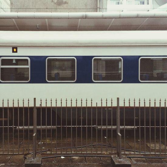 Side view of train across railing