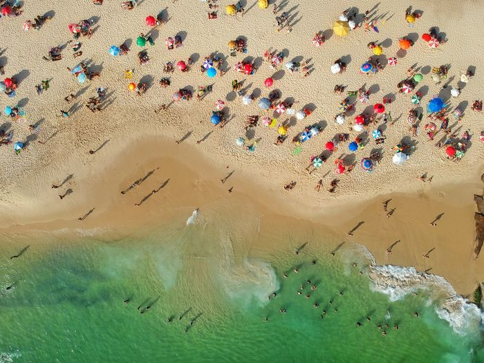 Aerial view of people enjoying on sand at beach