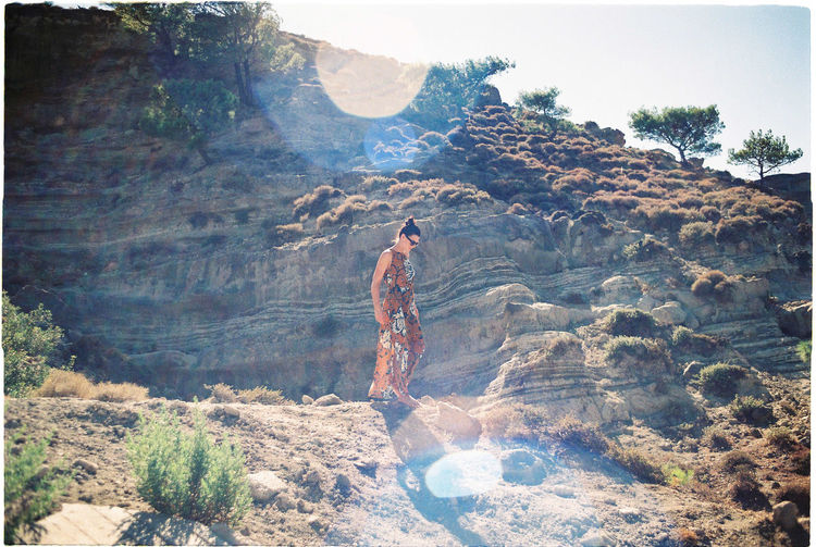 Fashionable Woman Walking On Dirt Against Rock Formation