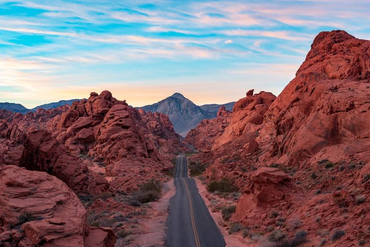 Empty country road amidst rock formations in desert against sky during sunset