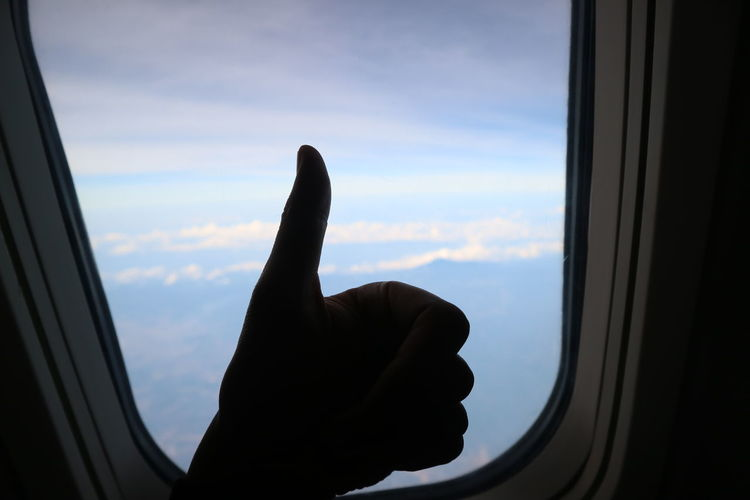 Cropped image of person hand against sky seen through window