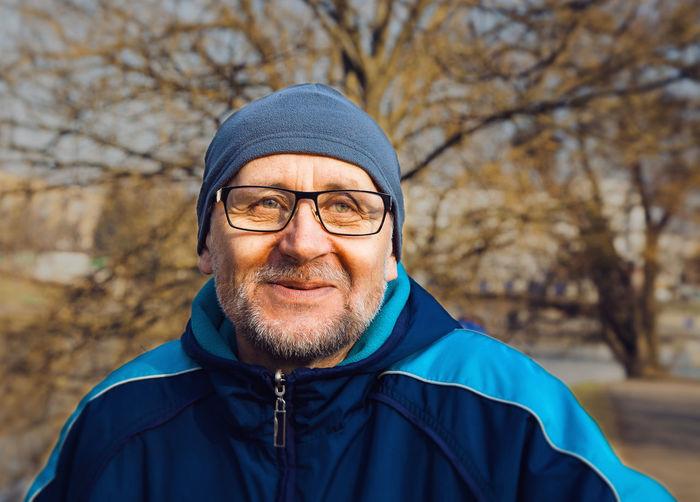 Close-up of man in eyeglasses looking away at park