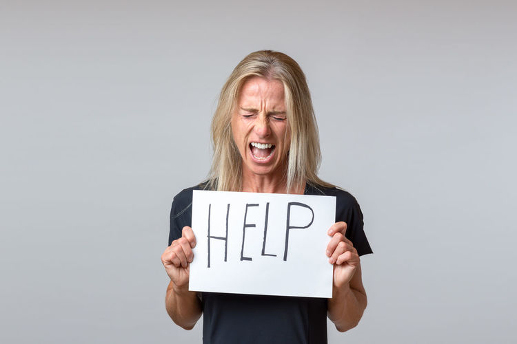Mature woman shouting while holding help sign against gray background
