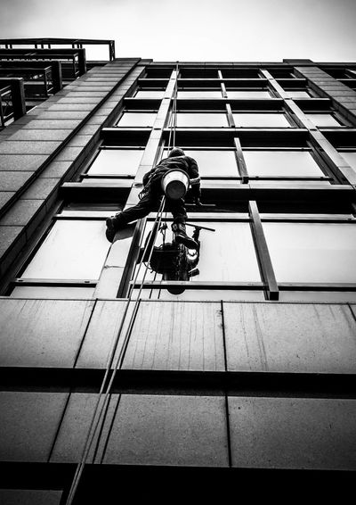 Low angle view of window washer on rope