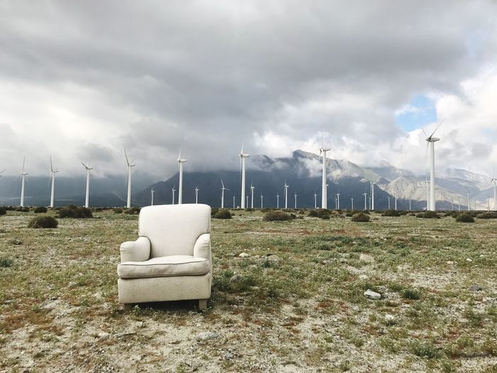 Empty Armchair And Windmill On Landscape Against Cloudy Sky