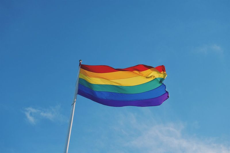 Low Angle View Of Rainbow Flag Against Blue Sky