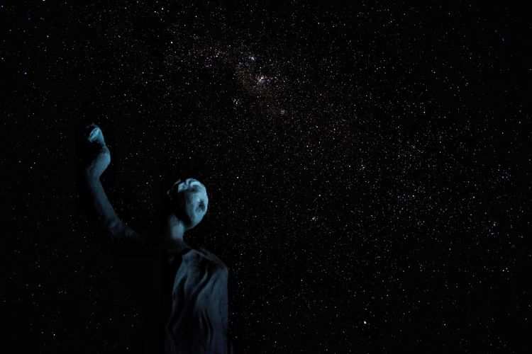 Low angle view of man against star field at night