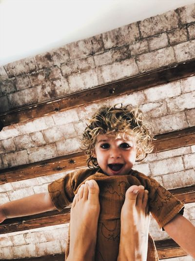 Portrait of smiling girl on wood against brick wall