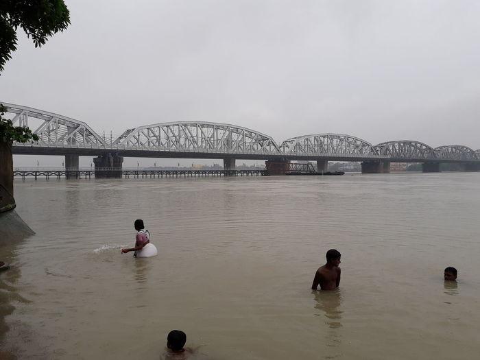 People on bridge over river against sky