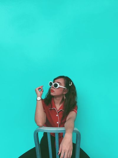 Young woman wearing sunglasses sitting against blue wall