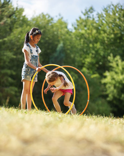 Friends Playing With Plastic Hoops On Field
