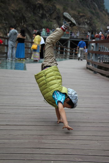 Side view of girl performing handstand on wooden bridge