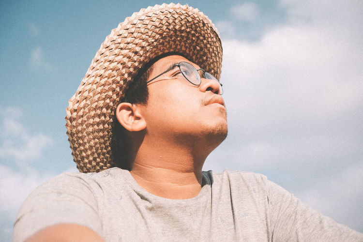 Low angle portrait of man wearing hat against sky