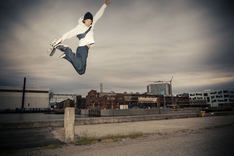 Low angle view of man jumping in city against sky