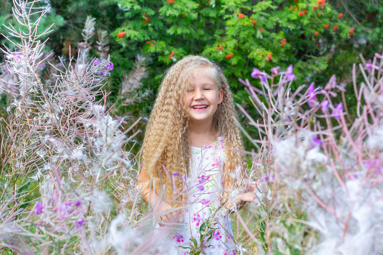Portrait of smiling girl with purple flowering plants