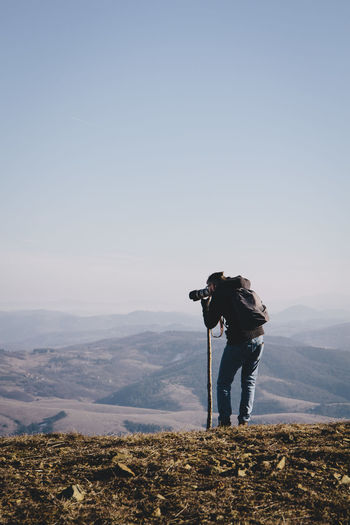 Rear view of man photographing from mountain against clear sky