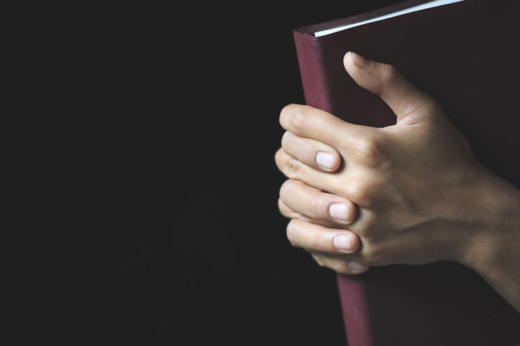 Close-up of hand holding book against black background