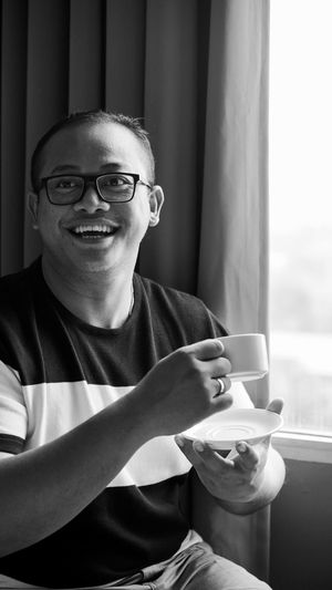 Smiling man sitting with coffee cup by window