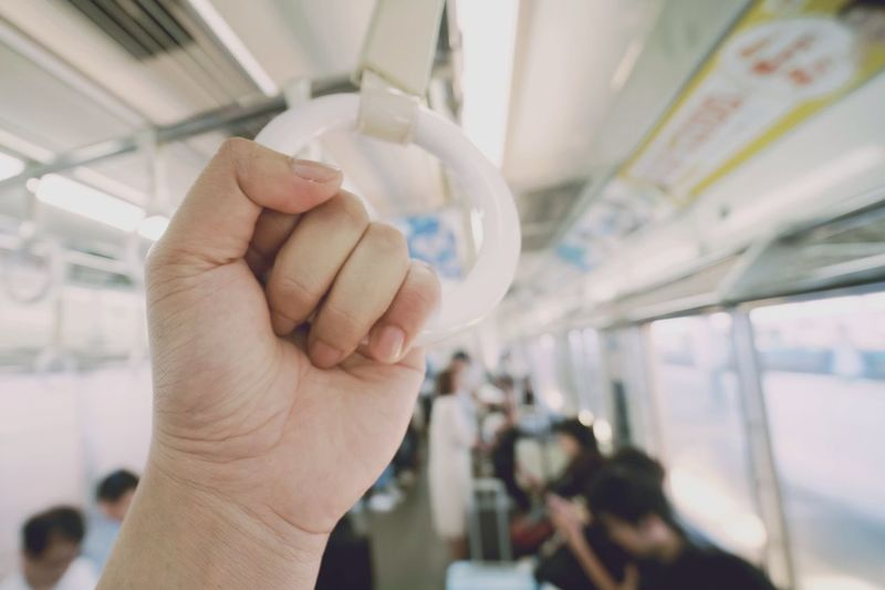 Cropped hand holding handle in bus