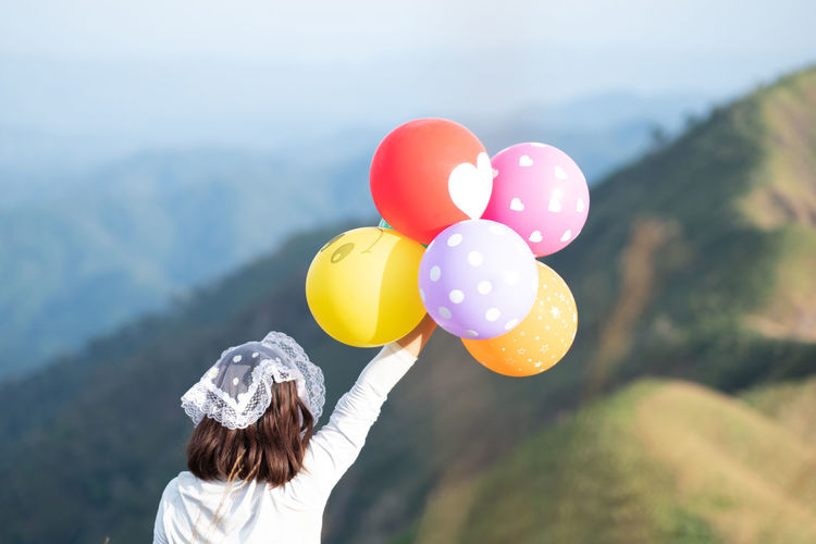 Rear view of woman holding balloons