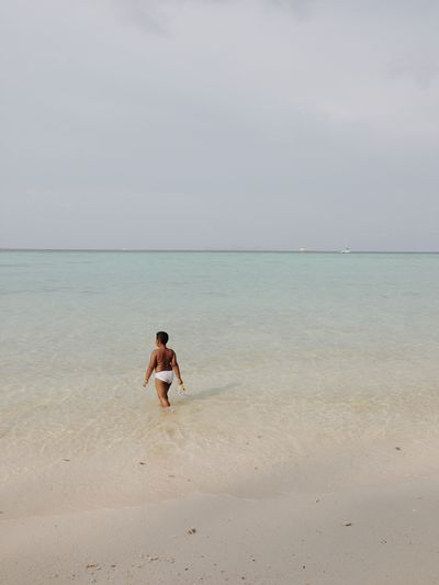 Rear View Of Boy Walking At Beach