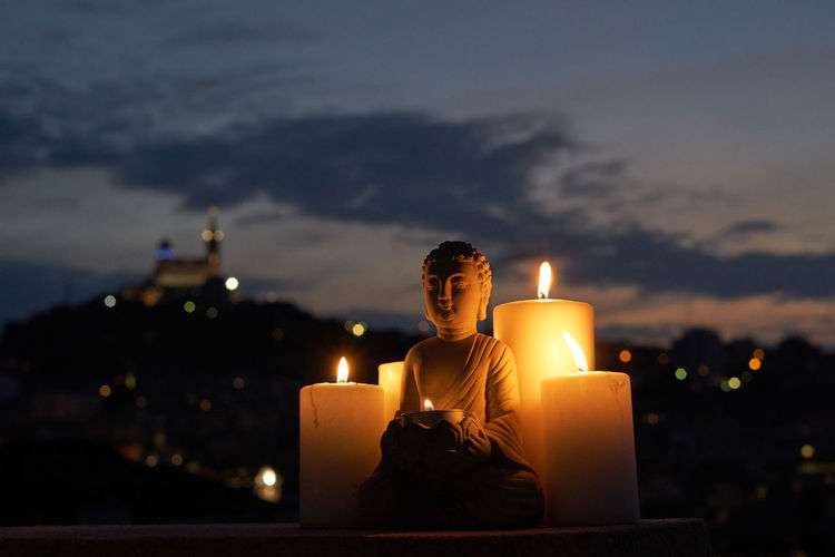 Lit tea light candles and budha against sky at night
