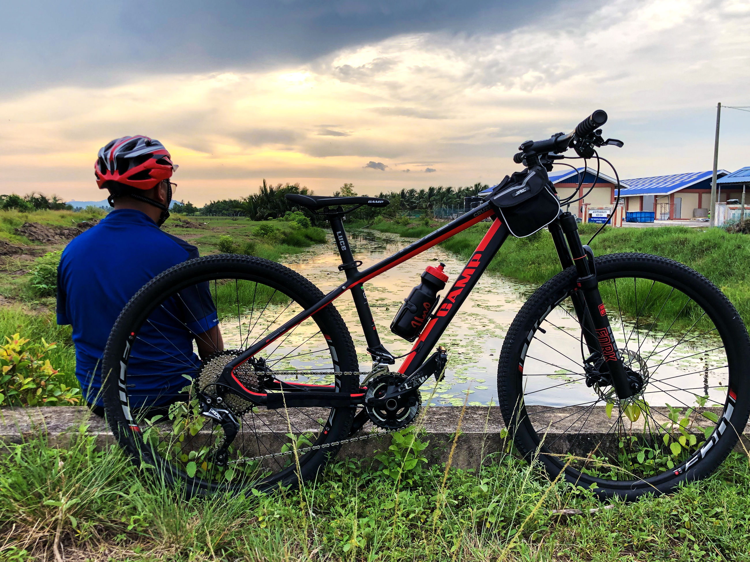 bicycle, transportation, cloud - sky, sky, grass, nature, plant, field, land vehicle, helmet, mode of transportation, land, real people, lifestyles, men, leisure activity, people, day, headwear, casual clothing, outdoors, wheel, riding