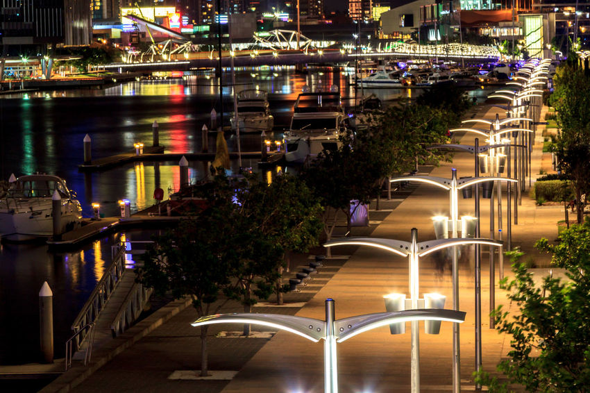 A line of lamp posts looking from the Docklands into Melbourne city Architecture Bridge Building Building Exterior Built Structure Canal City Illuminated Luxury Motion Nature Night No People Outdoors Plant Reflection Swimming Pool Transportation Travel Destinations Tree Water Waterfront