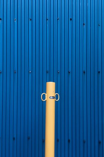 Beige pole against blue corrugated iron