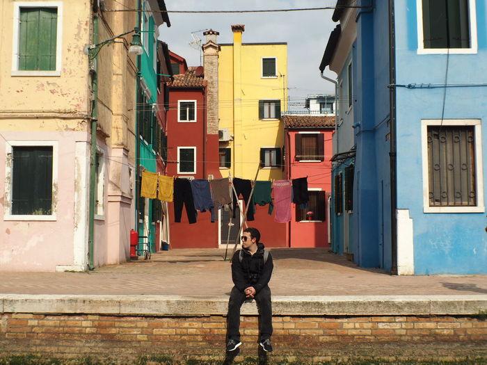 Full length of man sitting against buildings