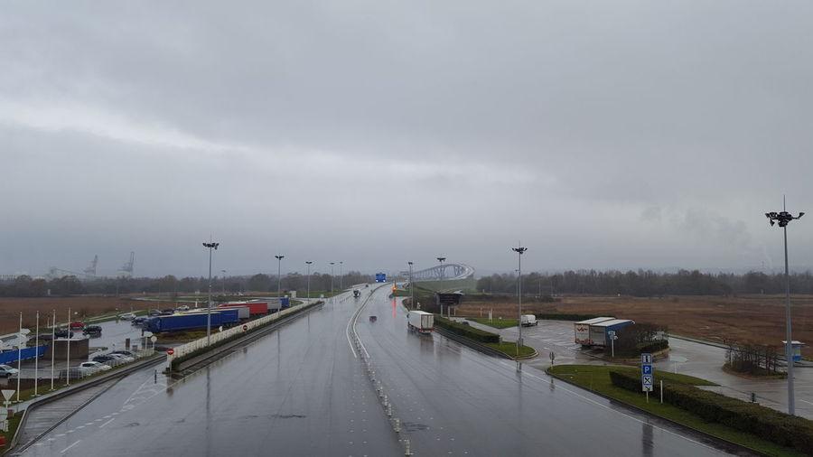 Vehicles on road against sky during rainy season