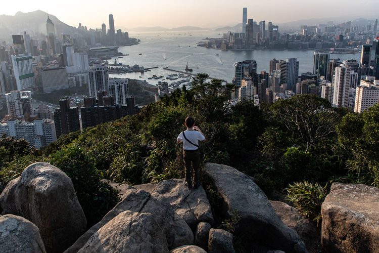 Rear view of man looking at city while standing by rocks against sky during sunset