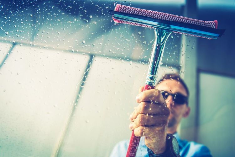 Caucasian Men Removing Water From His Car Window Right After Washing. Vehicle Window Cleaning Theme. Car Wash Cleaning Driver Washing Adult Clean Glasses Headshot Men Motion One Person Tool Water Wet Window
