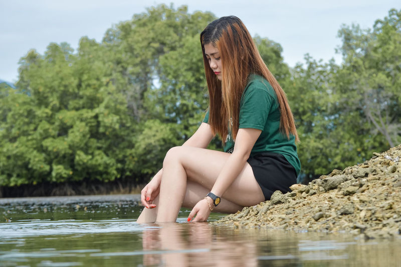 Midsection of woman sitting by lake against trees