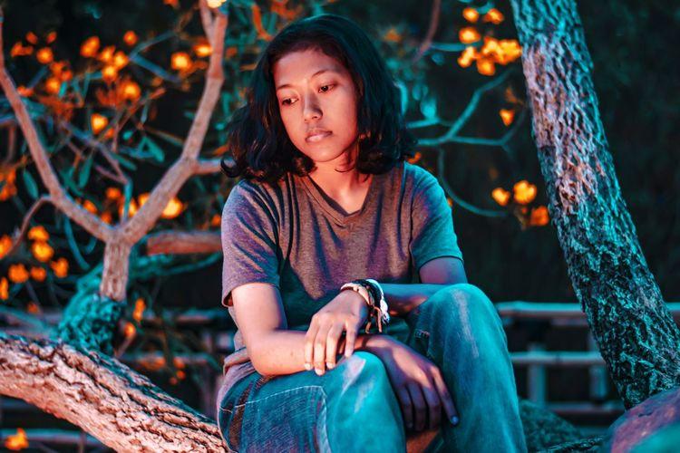 Portrait of girl sitting at illuminated night