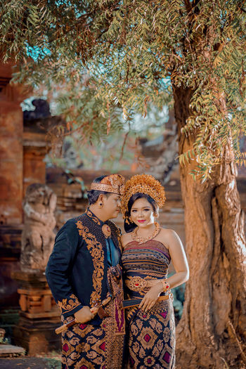 Balinese couple standing against tree wearing balinese traditional clothes