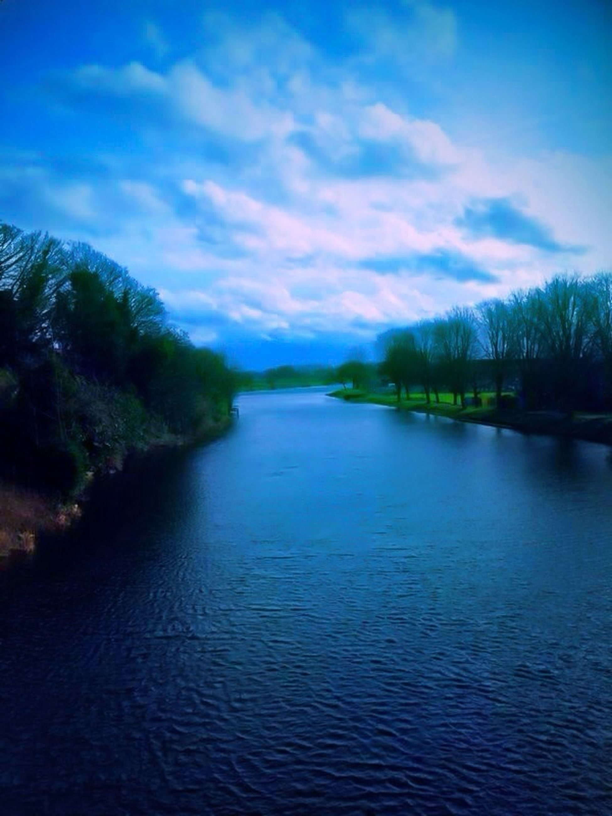 water, the way forward, sky, diminishing perspective, transportation, blue, vanishing point, tranquility, reflection, tranquil scene, nature, waterfront, beauty in nature, scenics, cloud - sky, lake, road, narrow, river, outdoors