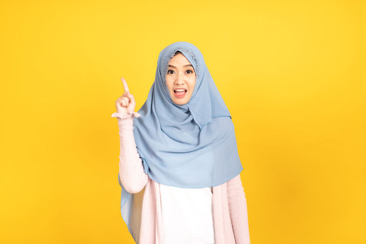 Young woman wearing mask against yellow background