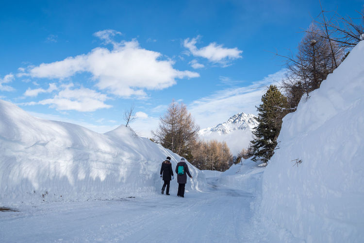 Rear View Of Friends Walking On Snow Covered Landscape