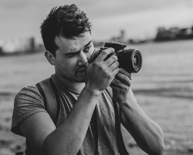 Young Man Photographing With Digital Camera At Beach
