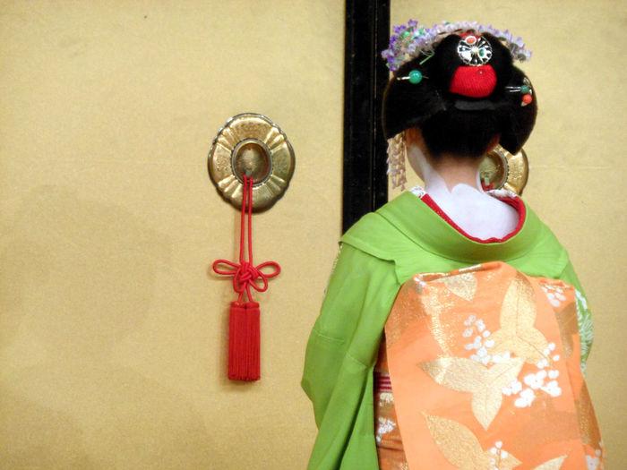 Rear view of geisha walking towards door