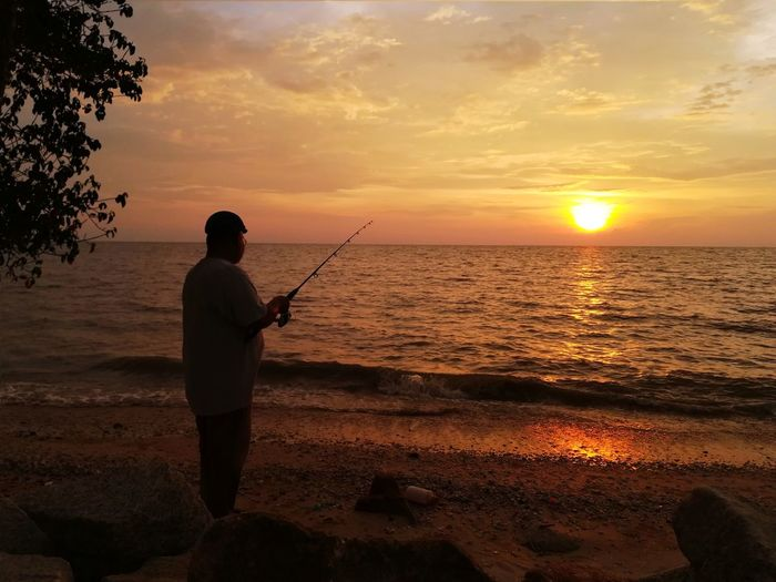 Rear view of a man fishing in sea at sunset