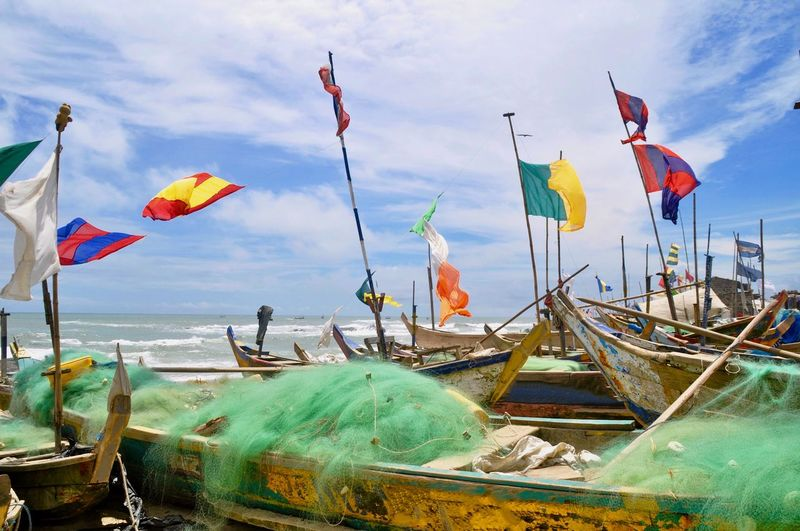 Panoramic view of boats moored at beach against sky